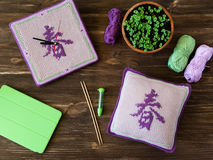Gebreide met de hand gemaakte horloges, vierkant hoofdkussen, naalden en lilac, groene, witte garenballen op houten lijst Vertali Stock Fotografie