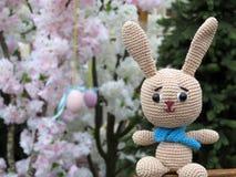 Gebreide Paashaas op de achtergrond van feestelijke de lentedecoratie stock afbeelding