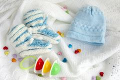 Gebreide pasgeboren babybuiten en hoed met kleurrijke rammelaar op gehaakte algemene witte achtergrond met kleurrijke harten Royalty-vrije Stock Foto's