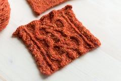 Gebreide roodbruine vierkante tapijt en garenbal op houten lijst Stock Afbeelding