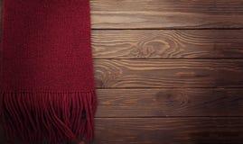 Gebreide sjaal van de kleur van Bourgondië op een donkere houten achtergrond Stock Foto's