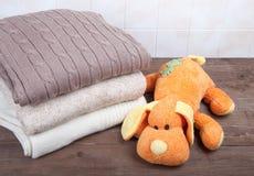 Gebreide stuk speelgoed hond en stapel van het breien van kleren op houten lijst op Royalty-vrije Stock Foto