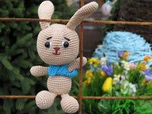 Gebreide stuk speelgoed Paashaas op de lente feestelijke achtergrond stock afbeeldingen