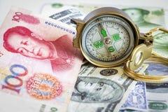 Gebrekkig die kompas op de dollar en yuansbankbiljetten wordt geplaatst Het bureau van C royalty-vrije stock foto