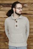 Gebrilde manier jonge mens met baard in jeans en trui op houten achtergrond Stock Foto's