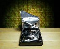 Gebrochen dem Festplattenlaufwerk vom Computer im Hintergrund von Th Stockbild