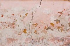 Gebrochene und strukturierte alte hellrosa Wand stockfoto