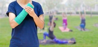 Gebrochener Arm mit Grünform auf unscharfer Fraueneignungsgruppe - Yoga Lizenzfreie Stockfotos
