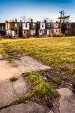 Gebrochener Bürgersteig und verlassene Reihenhäuser in Baltimore, Maryland Lizenzfreie Stockbilder