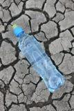 Gebrochener Boden mit Wasser in einer Flasche Stockbild