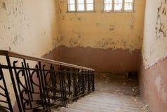 Gebrochener Gips am Treppenhaus in einer verlassenen Schule Stockbild