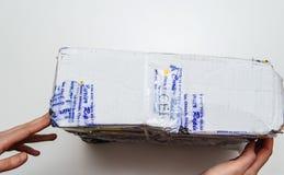 Gebrochenes Paket der Frau holdinng bedeckt mit Sicherheit schottischem adhesiv Stockbilder