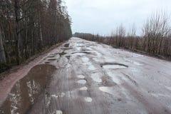 Gebroken asfaltweg met gaten en vulklei Stock Fotografie