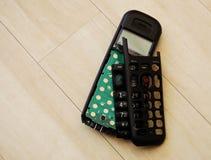 Gebroken telefoonzaktelefoon op houten vloer Royalty-vrije Stock Afbeeldingen