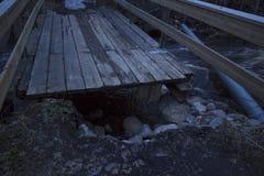 Gebroken brug van een de lentevloed van een gewoonlijk kleine rivier in een bos in noordelijk Zweden Stock Foto
