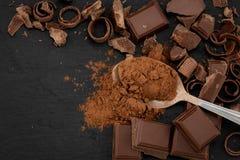 Gebroken chocoladestukken en cacaopoeder op een donkere achtergrond Hoogste Mening met Copyspace royalty-vrije stock fotografie