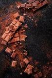 Gebroken chocoladestukken en cacaopoeder op marmer Royalty-vrije Stock Afbeeldingen