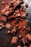 Gebroken chocoladestukken en cacaopoeder op marmer Royalty-vrije Stock Afbeelding
