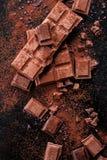 Gebroken chocoladestukken en cacaopoeder op marmer Stock Fotografie