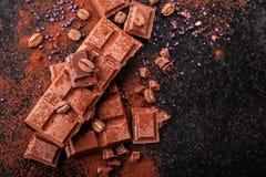 Gebroken chocoladestukken en cacaopoeder op marmer Stock Afbeeldingen