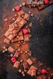 Gebroken chocoladestukken en cacaopoeder op marmer Stock Foto