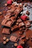 Gebroken chocoladestukken en cacaopoeder op marmer Stock Foto's