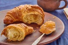 Gebroken croissant, lepel van appeljam en een kop Stock Foto