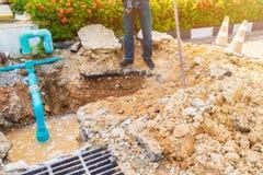 Gebroken de hoofdleiding van het de pijploodgieterswerk van de arbeidersreparatie Gebruiksschop om een gat op de weg ondergronds  stock afbeeldingen