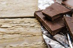 Gebroken donkere chocolade de zilveren verfrommelde folie Royalty-vrije Stock Afbeeldingen