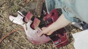 Gebroken gitaar op het gras voorraad Het concept het vergeten van klassieke muziek stock footage