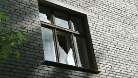 Gebroken glas in het raamkozijn Vernietiging of schade aan publiek of privé-bezit Voorgevel van een verlaten Gebouw stock footage