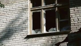Gebroken glas in het raamkozijn Voorgevel van een verlaten Gebouw Vernietiging of schade aan publiek of privé-bezit stock footage