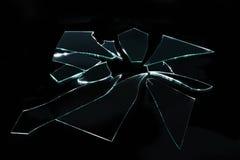 Gebroken glas met scherpe stukken op zwarte achtergrond Stock Afbeeldingen