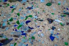 Gebroken glasflessen op wit zand De flessen is groene en blauwe kleur Afval op het zand Ecologisch probleem royalty-vrije stock afbeelding