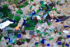 Gebroken glasflessen op wit zand De flessen is groene en blauwe kleur Afval op het zand Ecologisch probleem royalty-vrije stock fotografie