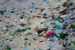 Gebroken glasflessen op wit zand De flessen is groene en blauwe kleur Afval op het zand Ecologisch probleem stock foto