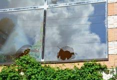 Gebroken glasvenster die op bewolkte hemel wijzen Een huisvenster met a royalty-vrije stock afbeeldingen