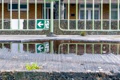 Gebroken groen nooduitgangteken en zijn gedachtengang van een puddl stock foto