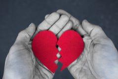 Gebroken hart in de handen - scheidingsconcept zwart-wit foto met rood hart blak en wit stock afbeelding