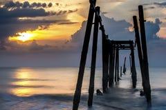 Gebroken houten brug en golven die op overzees bij tijdens zonsondergang, Phangnga, Thailand verpletteren Stock Afbeeldingen