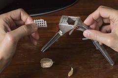 Gebroken knoflookpers in mannelijke handen royalty-vrije stock foto's
