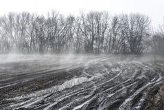 Gebroken landweg op een landbouwgebied in de vroege lente royalty-vrije stock afbeelding