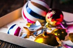 Gebroken oude uitstekende Kerstmisballen met kartondoos Stock Afbeeldingen