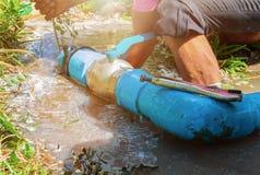 Gebroken pijp in gat met watermotie bij kant van de weg en loodgieter het werk reparatie en het Sluiten van Buigtang stock fotografie