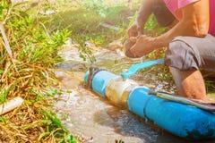 Gebroken pijp in gat met watermotie bij kant van de weg en loodgieter het werk reparatie en het Sluiten van Buigtang royalty-vrije stock fotografie