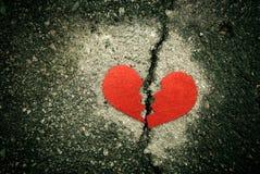 Gebroken rood hart op gebarsten asfalt Scheidingsconcept royalty-vrije stock foto's