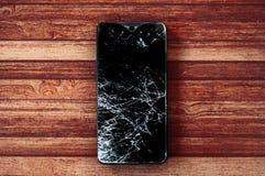 Gebroken smartphone met het realistische verbrijzelen van touchscreen op houten achtergrond Stock Foto