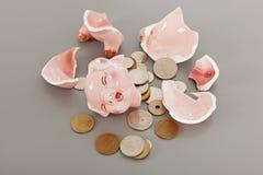 Gebroken spaarvarken met muntstukken Stock Afbeelding