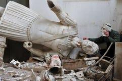 Gebroken standbeeld en mens met het fragment van het pleistermasker Stock Foto's