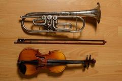 Gebroken trompet en viool op de houten vloer Royalty-vrije Stock Afbeeldingen